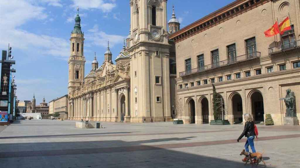 Una mujer pasea a su perro en la plaza del Pilar en Zaragoza.