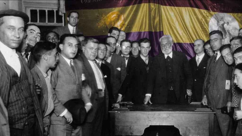 Miguel de Unamuno, en el centro, delante de una bandera republicana.