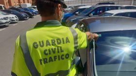 Un agente de la Guardia Civil comprobando si la pegatina de la ITV de un coche está vigente.