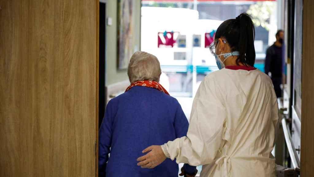 na trabajadora de la residencia de mayores Vitalia Canillejas ayuda a una paciente.