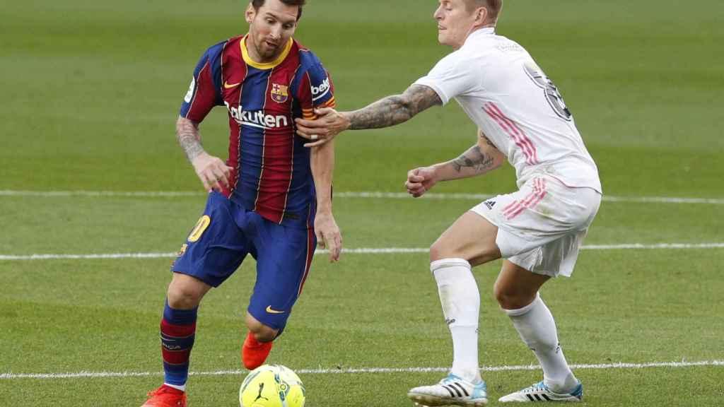 Toni Kroos y Leo Messi luchan por la posesión en El Clásico de La Liga