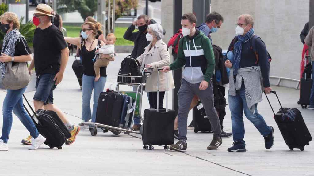Personas con mascarilla saliendo de un aeropuerto.