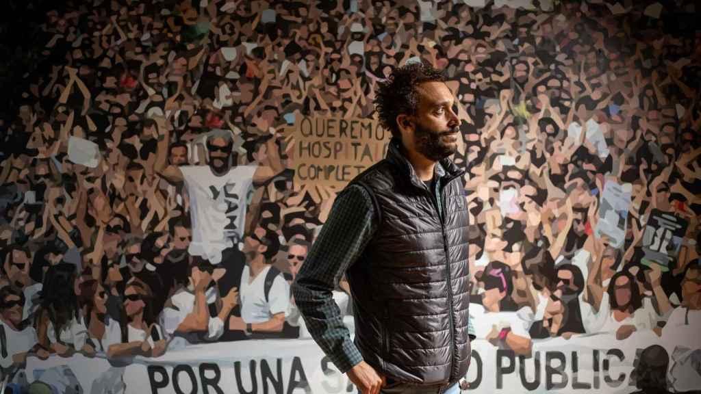 El médico granadino Jesús Candel, más conocido como Spiriman, ante un vinilo con una imagen de las manifestaciones multitudinarias que organizó contra la gestión de la sanidad pública andaluza.