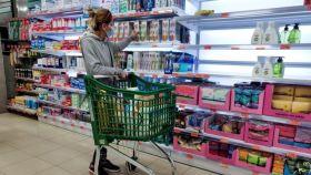 Una consumidora, en un supermercado, eligiendo un producto para su cesta de la compra.