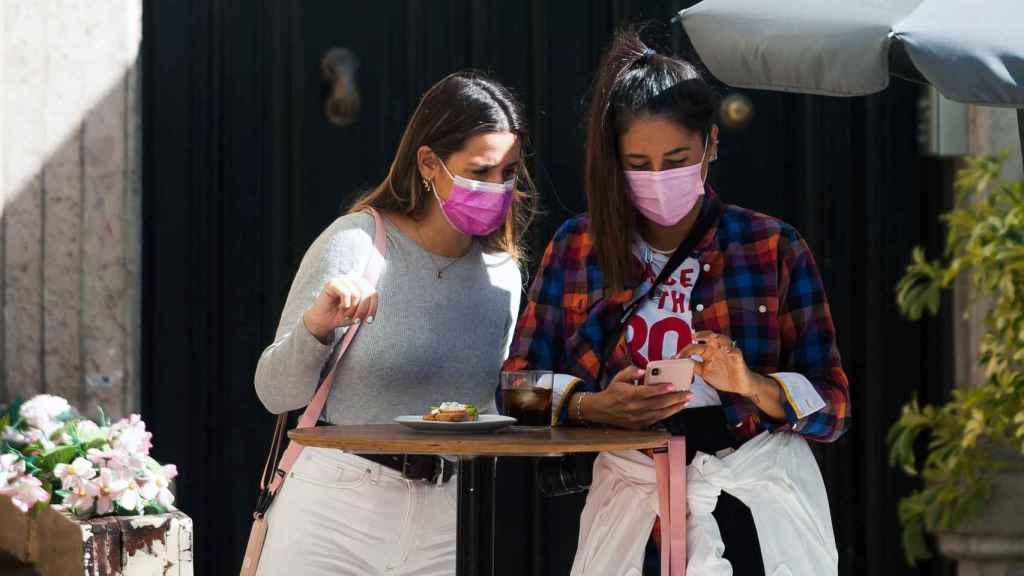 Dos jóvenes utilizando mascarillas en un bar.