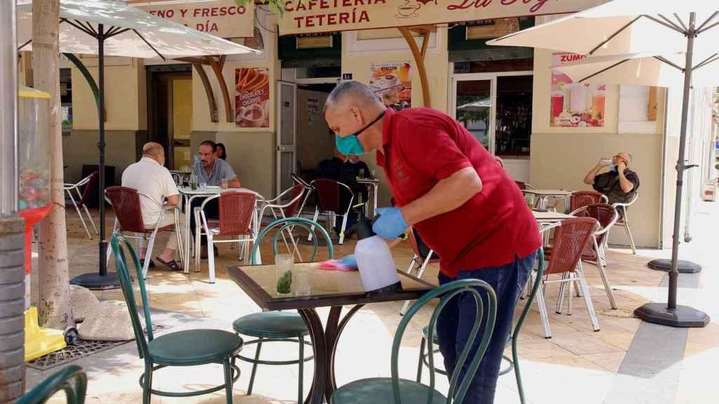 Un camarero prepara las mesas de una terraza.