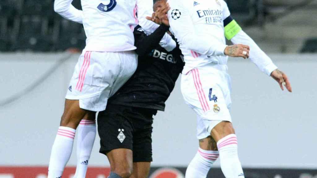 Sergio Ramos y Varane saltan para impedir que un jugador del Moenchengladbach se lleve el balón
