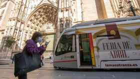 Una mujer con mascarilla pasea por delante de la Catedral de Sevilla.