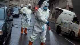 Operarios municipales realizan labores de desinfección en una calle de Orense.