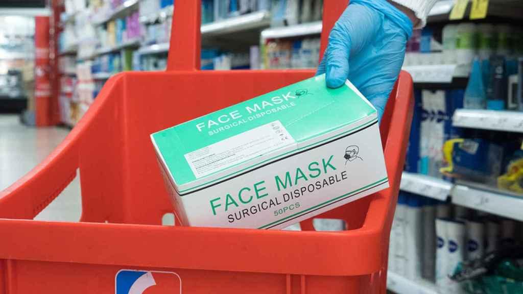 Una persona adquiere un paquete de mascarillas en un supermercado Eroski.