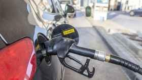 Un coches repostando diésel en una gasolinera.