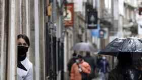 Una empleada de un local en una calle turística observa a los turistas en Santiago de Compostela.