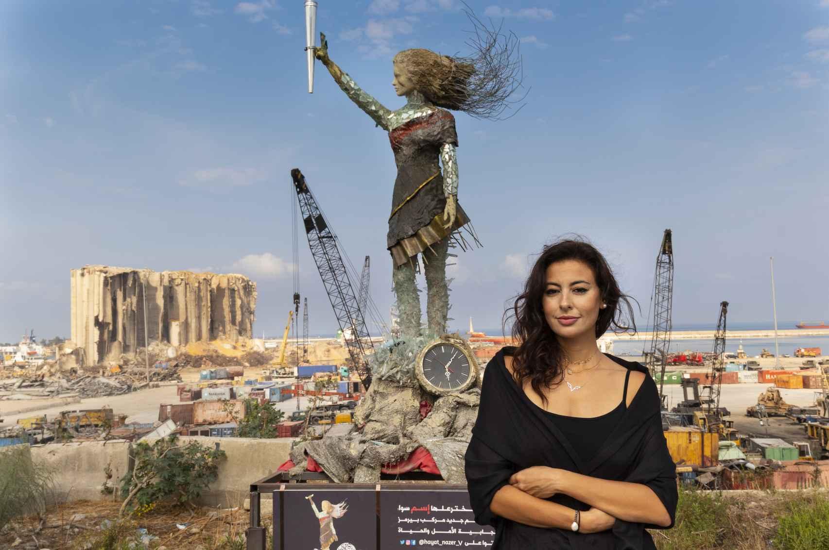 Hayat Nazer en el puerto de Beirut destruido por la explosión, junto a la escultura de la niña.