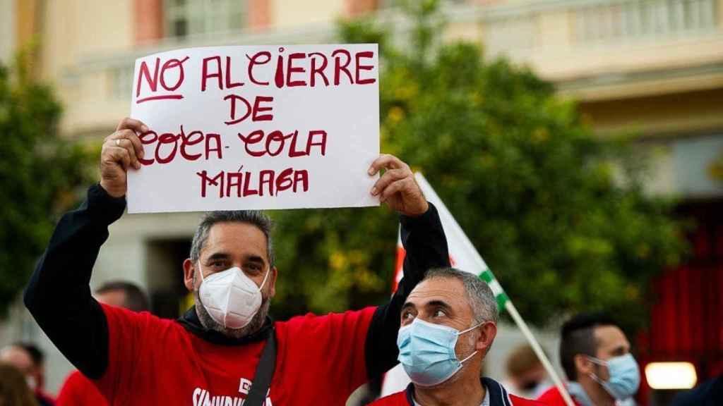 Un trabajador con una pancarta en la concentración contra el cierre de la planta de Coca-Cola en Málaga.
