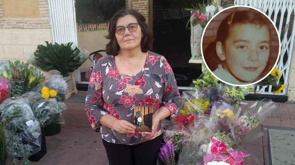 María sujeta una foto de su difunta hermana, Toñi -en el círculo-, en un puesto de flores habilitado en Campos del Río.
