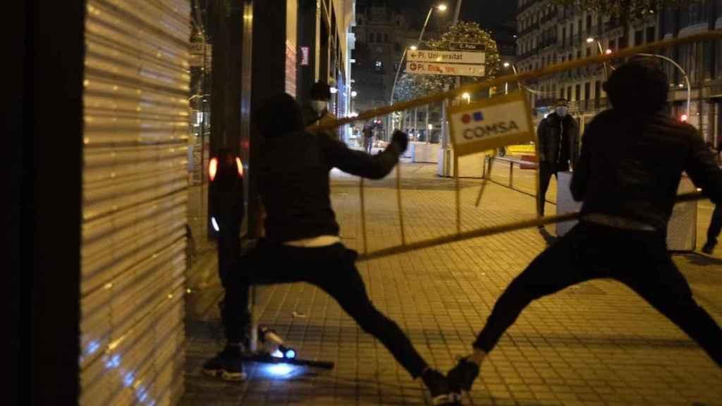 Dos hombres lanzan una valla contra un escaparate en Barcelona.