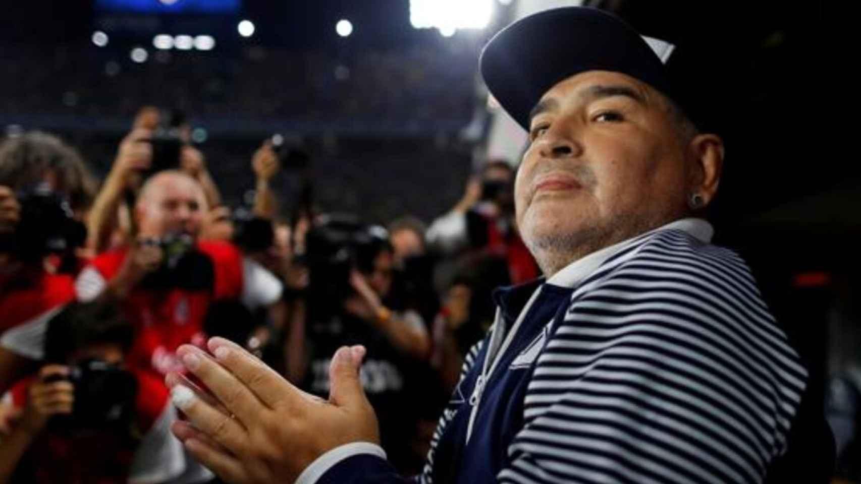 Diego Armando Maradona, siendo fotografiado en el banquillo