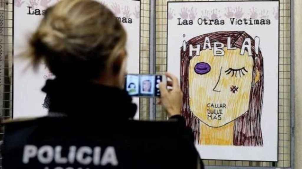 Una agente de la Policía Local fotografía un cartel contra la violencia machista.