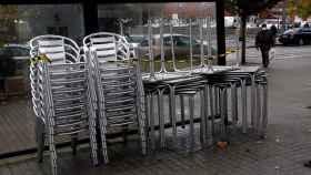 Vista de las sillas y las mesas apiladas en una terraza cerrada este lunes en la localidad de Narón.