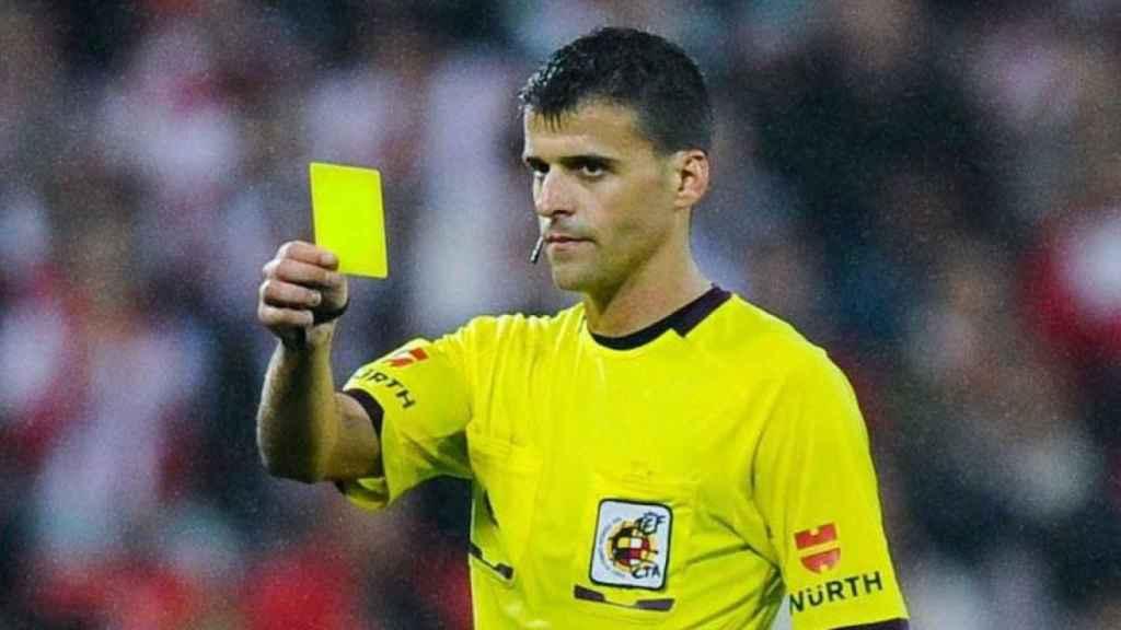 Jesús Gil Manzano, enseñando una tarjeta amarilla en un partido de La Liga