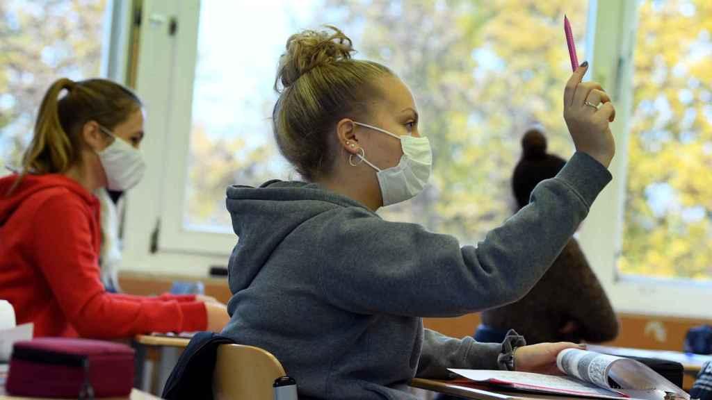 Una alumna alemana con mascarilla y dudas pregunta al profesor.