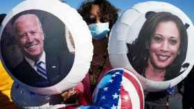 Una mujer celebrando la victoria con dos globos de Biden y Harris.