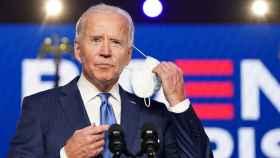 Joe Biden se quita la mascarilla antes de comenzar su rueda de prensa.