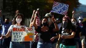 Tres chicas jóvenes con carteles contra Trump.