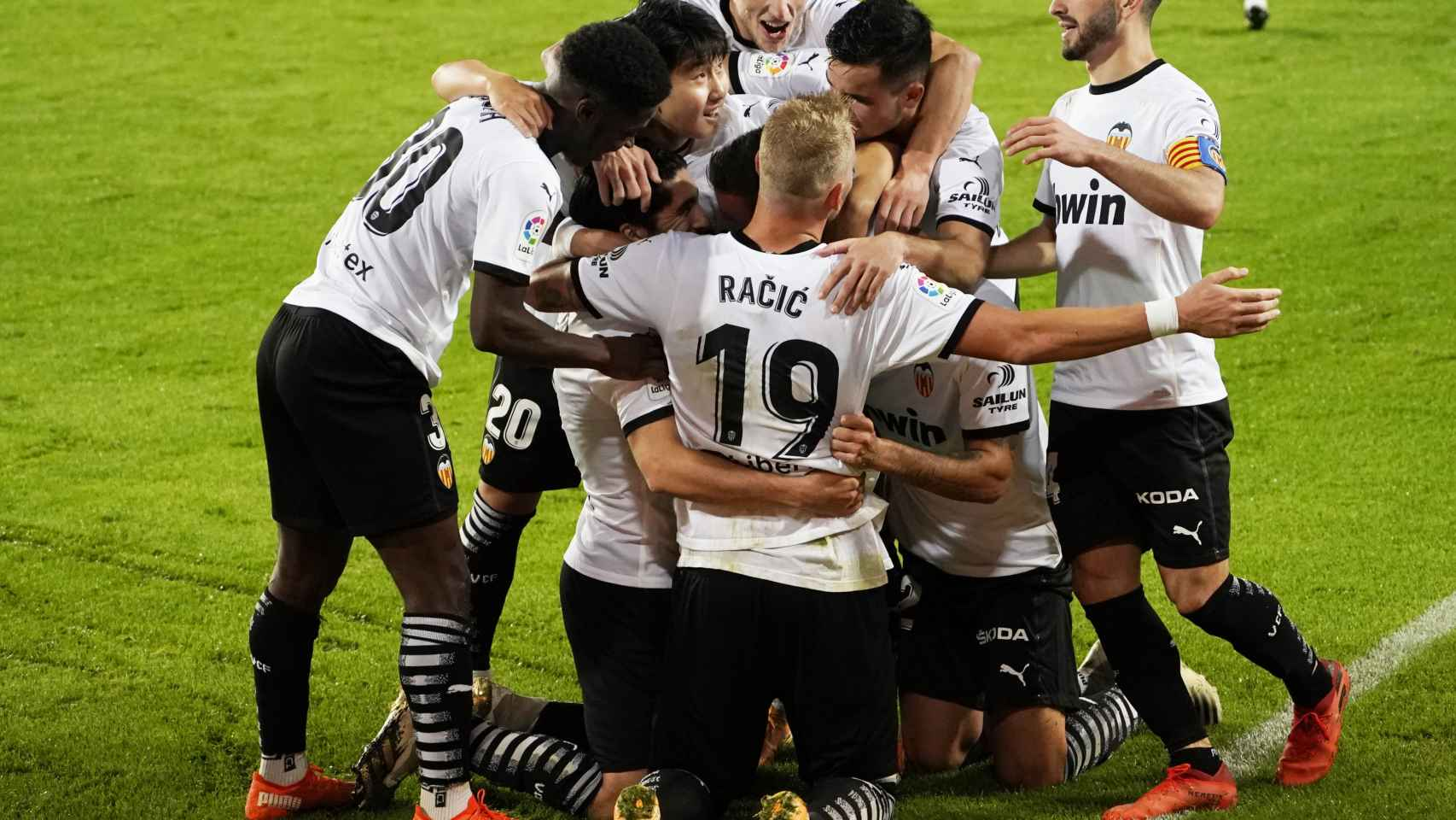 Los jugadores del Valencia felicitan a Soler por su tercer gol de penalti al Real Madrid