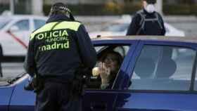 Un policía pone una multa de tráfico.