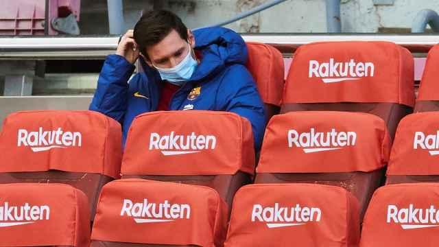 Leo Messi espera en el banquillo con mascarillas situado en la grada del Camp Nou durante la pandemia por la Covid-19