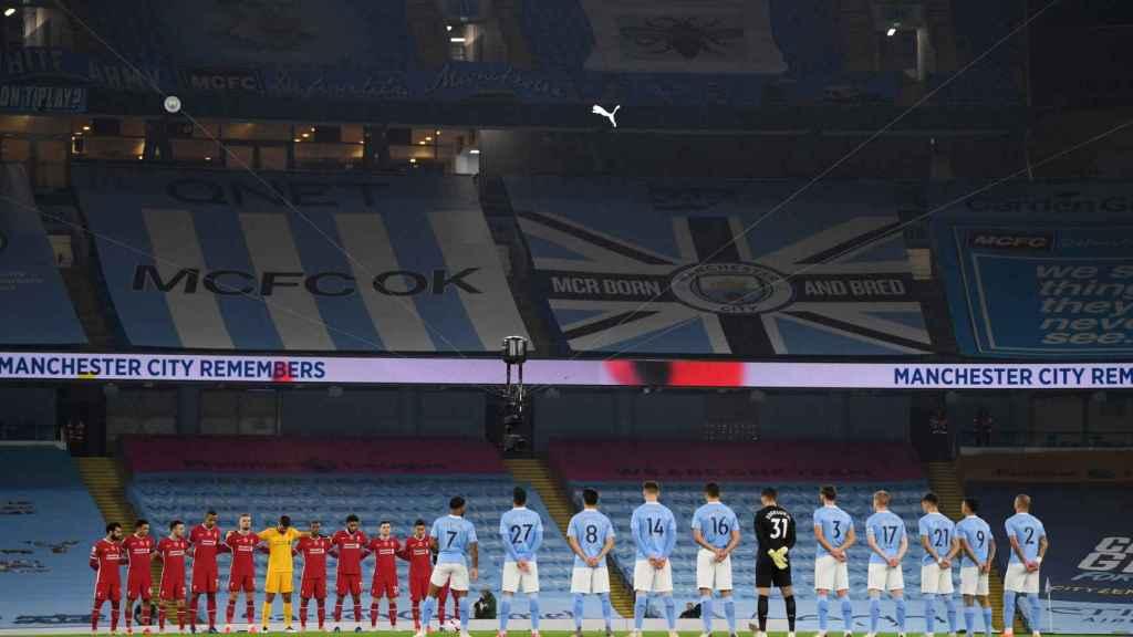 Los jugadores de Liverpool y Manchester City, durante un minuto de silencio en el Etihad Stadium con las gradas vacías