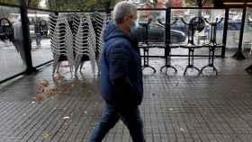 Un hombre camina por delante de las sillas y las mesas apiladas en una terraza cerrada.