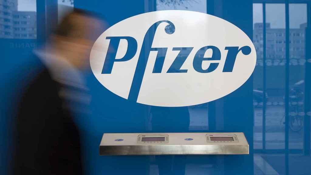 Un hombre pasa ante un logotipo de Pfizer.
