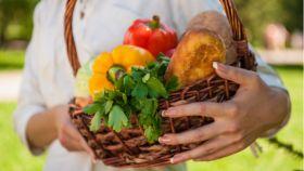 Una mujer sostiene verduras y hortalizas beneficiosas para la salud.