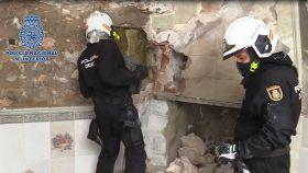 Los agentes abren la pared tras la que estaba el coche desguazado.