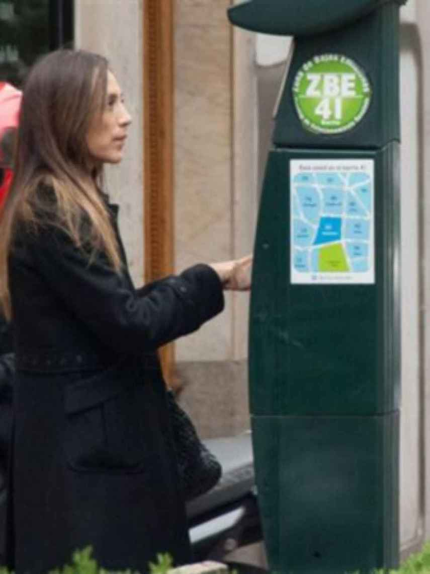 Tamara pagando la multa en el parquímetro.