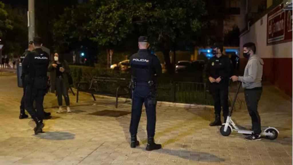 Agentes de la Policía Nacional, junto a un usuario de patinete eléctrico.