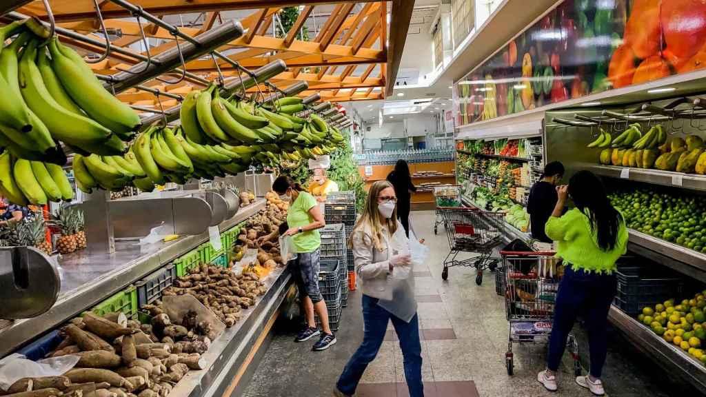 Clientes que recorren el pasillo de un supermercado, en Caracas.