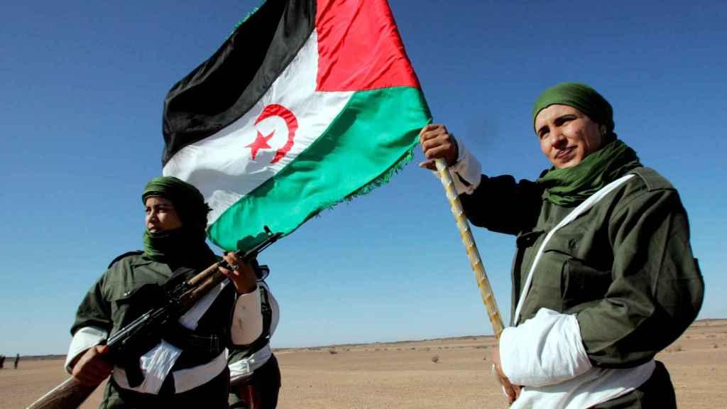 Una mujer soldado saharaui porta una bandera de la República Árabe Democrática del Sahara.
