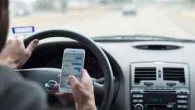 Un conductor utilizando su teléfono en el interior del coche.