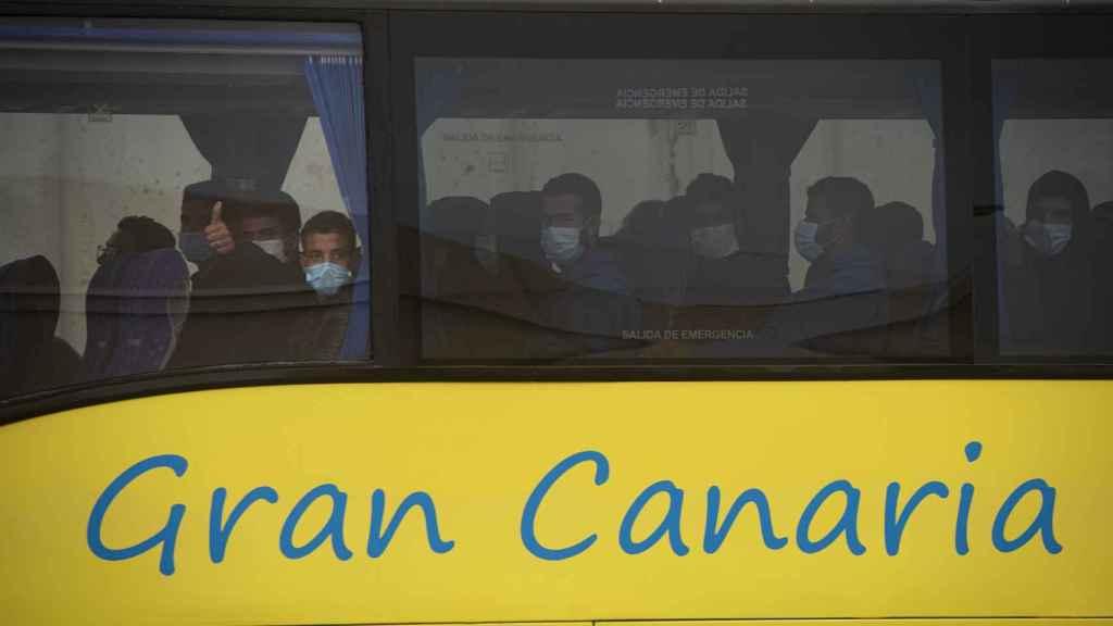 Un autobús traslada este viernes a medio centenar de inmigrantes fuera del muelle del puerto de Arguineguín.
