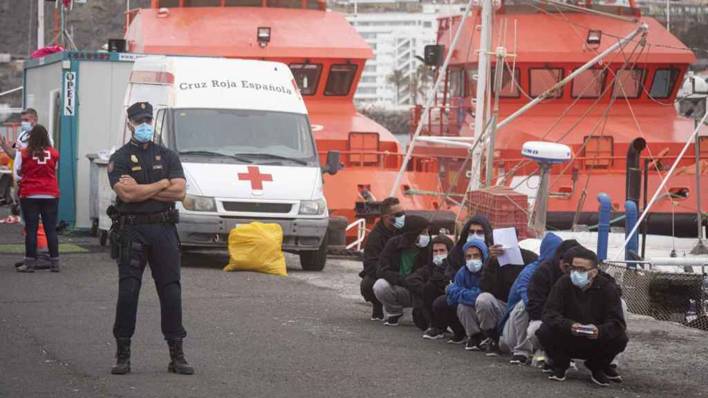 Un policía custodia a un grupo de inmigrantes que espera su traslado fuera del muelle de Arguineguín.