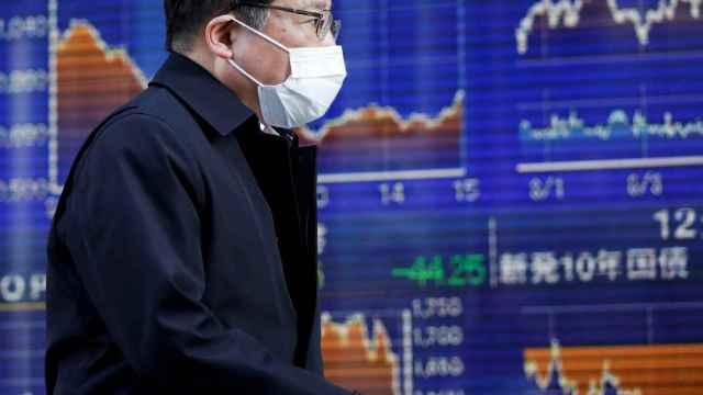 Un bróker pasa por delante de unas pantallas de negociación en la Bolsa de Tokio.