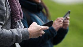 Dos personas usando su teléfono móvil.