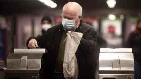 Un hombre, en el Metro de Madrid, usando una mascarilla quirúrgica.