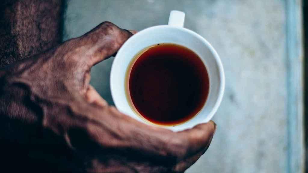Un hombre sujetando una taza de té rojo.