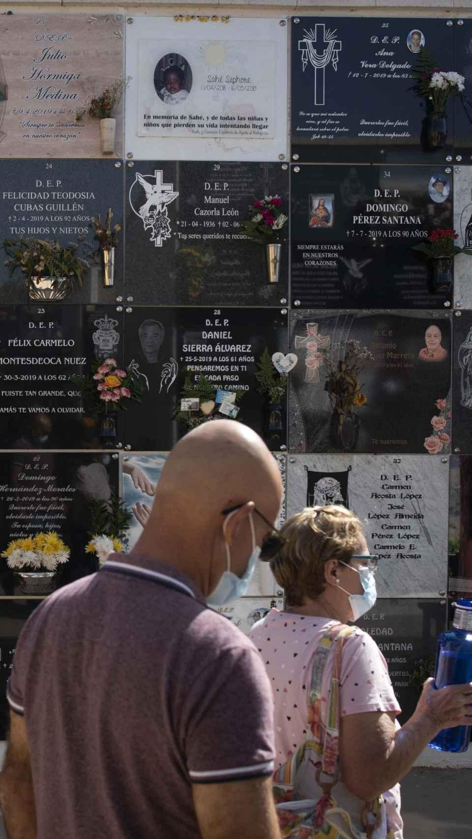 Dos personas pasan por delante de la lápida de Sephora, la niña de 13 meses enterrada en el cementerio de Vecindario.