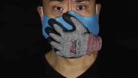 El artista Edmond Kok, de Hong Kong, con una mascarilla que representa la pérdida de voz/ Vincent Yu