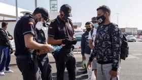 Agentes de Policía toman los datos a varios inmigrantes en Santa Cruz de Tenerife.